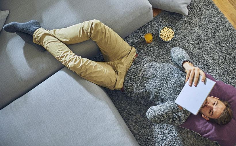 Mann liegt auf dem Rücken und liest E-Reader