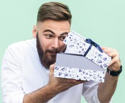 Mann guckt in Geschenk