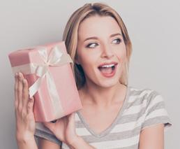 Frau schaut lachend Geschenk an