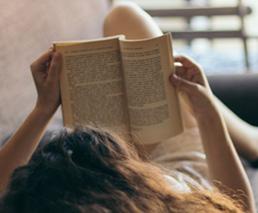 Frau liest Buch liegend