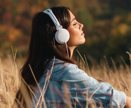 Frau hört Buch mit Kopfhörer im Feld