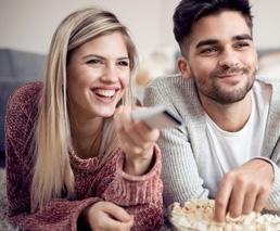 Pärchen schaut vergnügt Film mit Popcorn