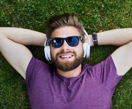 Mann hört Buch im Gras liegend