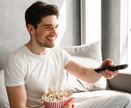 Mann schaut lachend Film im Bett mit Popcorn