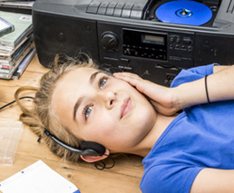 Mädchen hört Buch auf dem Boden liegend