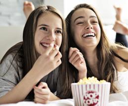 2 Mädchen schauen Film mit Popcorn