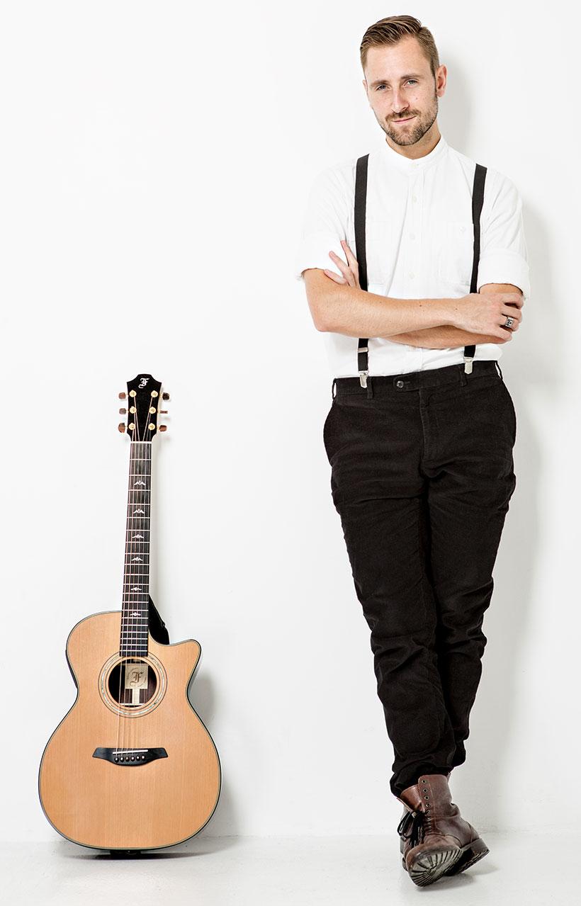 Kunz stehend neben einer Gitarre