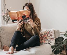 Romana liest Buch «Shantaram» auf dem Sofa