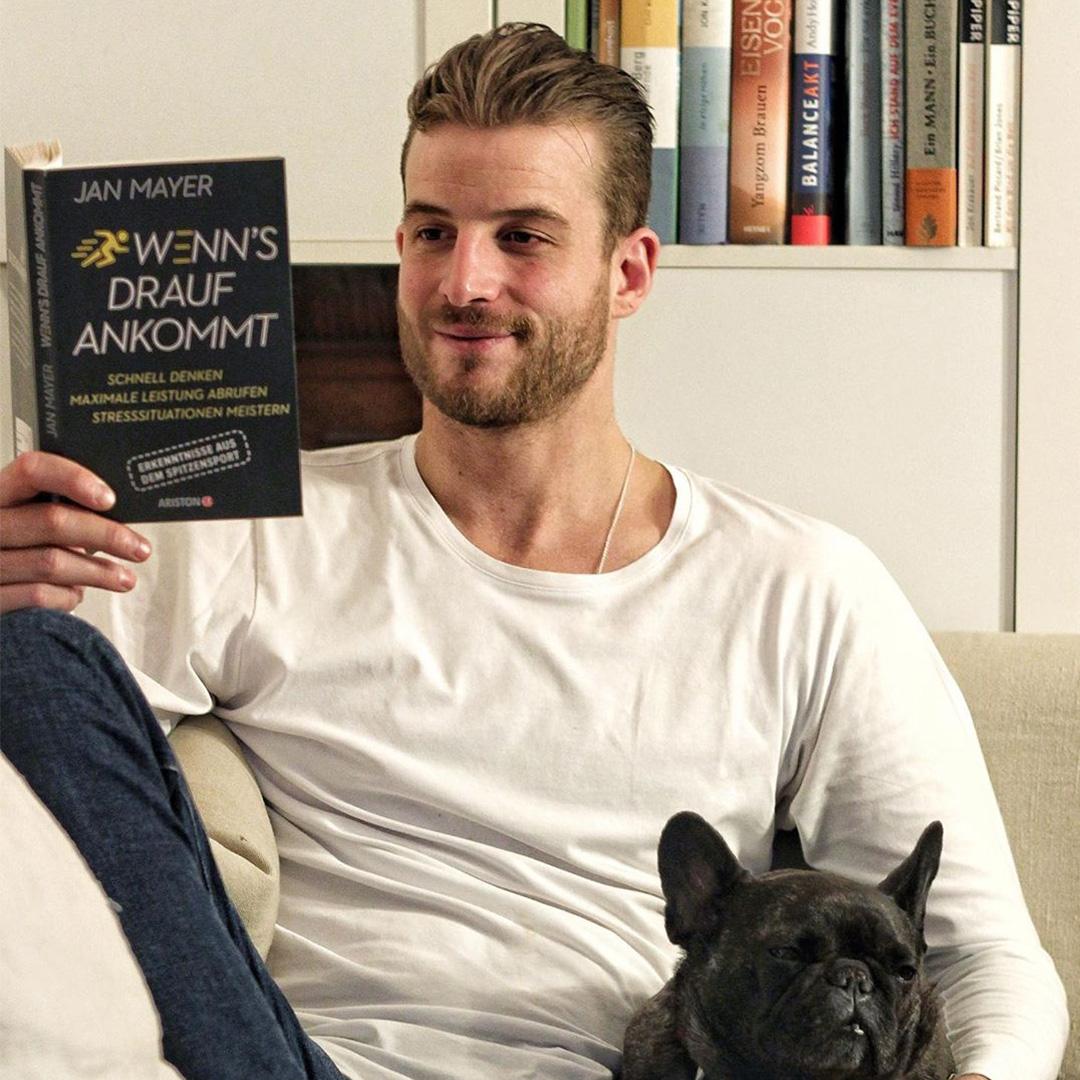 Janosch liest das Buch «Wenn's drauf ankommt» auf dem Sofa
